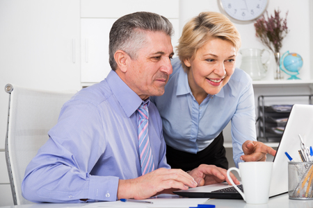 Mature man and woman watch interesting information on internet at ofice