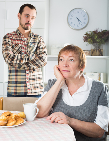 Mature mother was angry at her son and offended him at home Archivio Fotografico