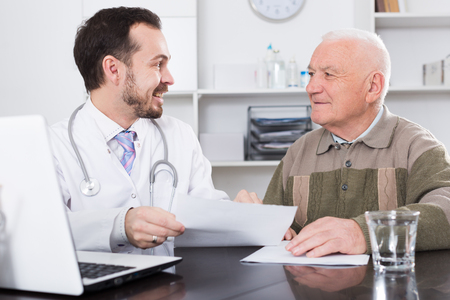 Elderly man comes to doctor in clinic for advice on health Фото со стока