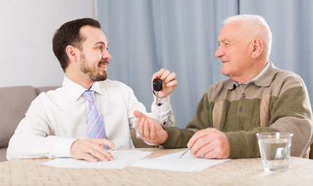 Elderly man and young man sign contract car rent and hand over keys