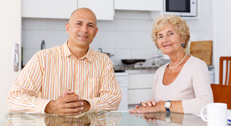 Man and his elderly mother having conversation at kitchen table Banco de Imagens