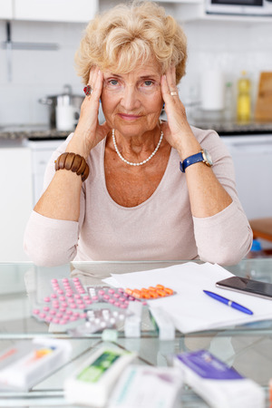 Confused senior woman sitting at kitchen table among a lot of medicines Standard-Bild