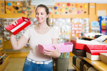Smiling woman choosing multi colored and other gift boxes at shop