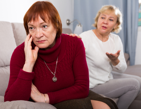 Portrait of mature females talking and quarreling on sofa indoors Imagens