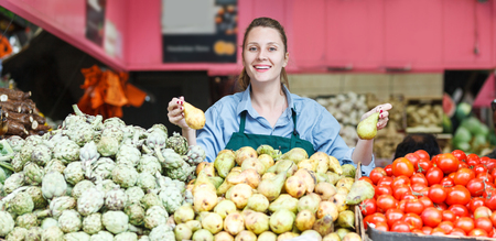 happy young female seller is standing near shelves with vegetables and fruits in the market. Zdjęcie Seryjne