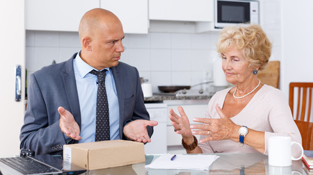 Sales agent spreading his hands, because he can not take back box of goods from mature woman