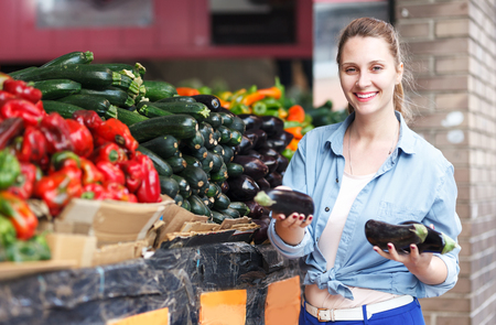 Portrait of positive woman who is choosing aubergine in the open air grocery Foto de archivo
