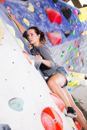 Portrait of young woman mountaineer climbing artificial rock wall without belay indoors