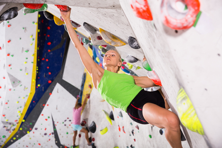 Positive woman mountaineer climbing artificial rock wall without belay at bouldering gym