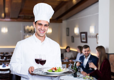 Smiling male chef with serving tray welcoming to restaurant Фото со стока