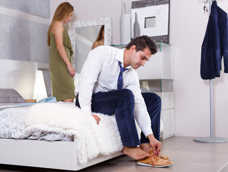 Man sitting on bed and dressing up while his girlfriend prinking in front of mirror