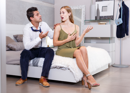 Young unhappy couple quarreling while sitting on bed in comfortable room Stockfoto