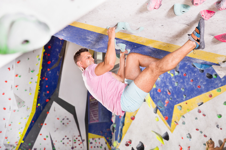 Confident male mountaineer climbing artificial rock wall without the belay indoors