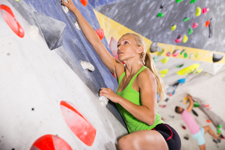 Young female alpinist practicing indoor rock-climbing on artificial boulder without safety belts Banco de Imagens - 113722413