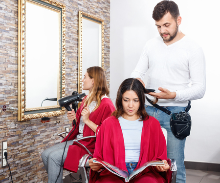Positive  cheerful smiling young man hairdresser cuts hair of young woman with magazine at salon 免版税图像 - 113778397