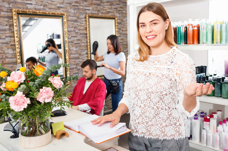 Portrait of young cheerful  woman  administrator inviting to beauty salon