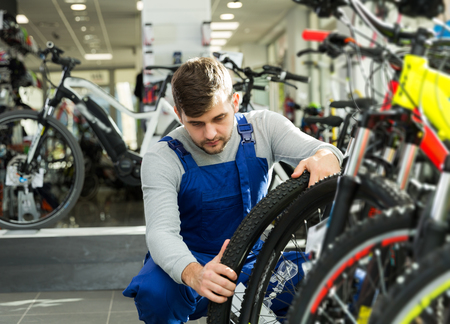 Portrait of young professional man checking tire on wheel in bicycle shop Reklamní fotografie - 113780008