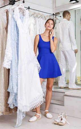 Happy young woman holding wedding dress and talking on her phone in wedding shop