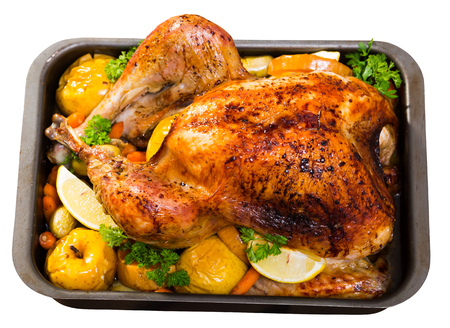 Whole roasted turkey with apples, pumpkin, potatoes, carrots and greens in baking dish. Isolated over white background