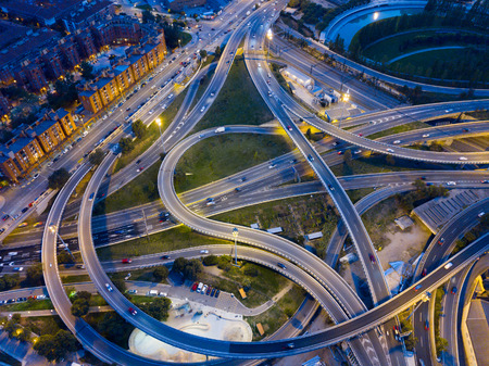 Night view from drone of lighted overpass interchange in modern town