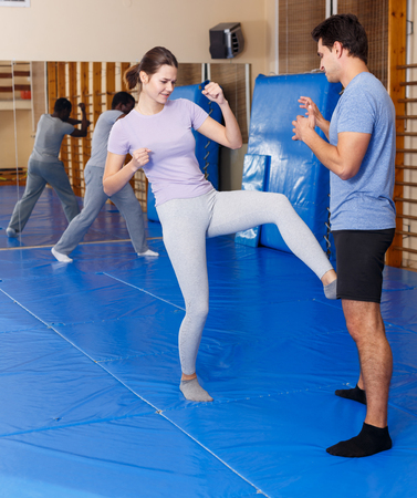 Adult people practicing effective techniques of self-defence in training room Stock Photo