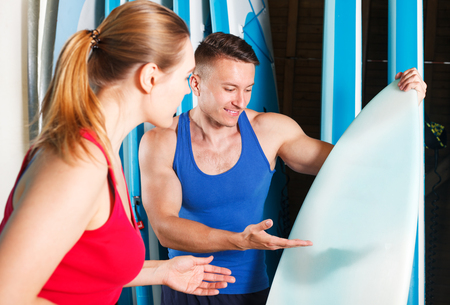 Young sporty couple choosing surf equipment for rent in surf club Stockfoto