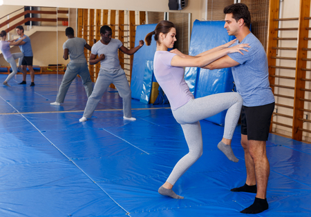 Young man and woman at self protection workout, training attack movements in pair