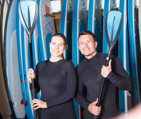 Portrait of smiling sporty guy and girl with paddles for surfing