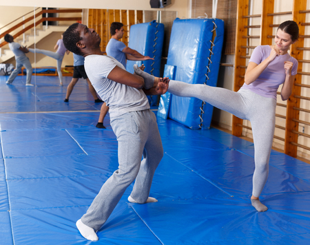 Young girl and African American man practicing self defense techniques in gym