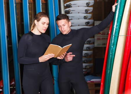 Two positive surf instructors making complete list of surfboards suitable for rent in surf club Stock fotó