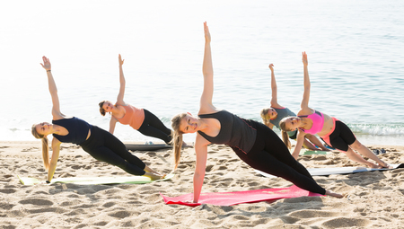 Young satisfied women exercising yoga poses on sunny beach by ocean