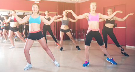 Group of young fitness females dancing modern zumba in dance class
