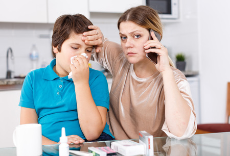 Worried woman using phone calling doctor while her son with running nose and tissue sitting nearby in kitchen