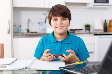 Portrait of boy doing homework and using mobile phone in kitchen at home
