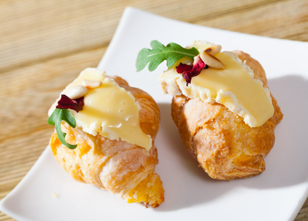 Dessert of french cuisine, mini croissant with camembert cheese at plate in cafe