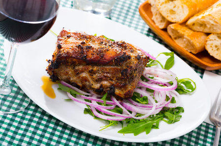 Delicious grilled rack of pork served with fresh arugula leaves and purple onion Stock Photo