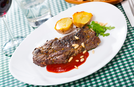 Delicious well done fried beef loin served with vegetable garnish of baked potato, tomato sauce and pine nuts