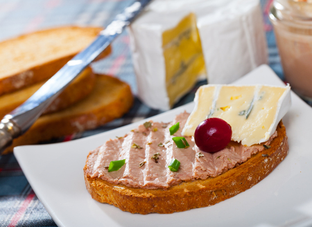 Delicate liver pate served on toasted bread with soft blue cheese and cranberry berry