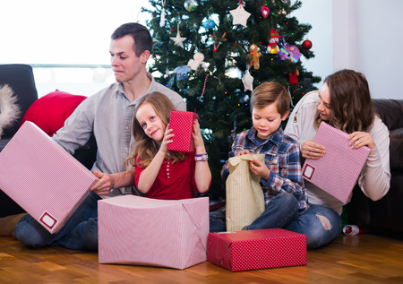 Large young family handing gifts to each other during Christmas at home
