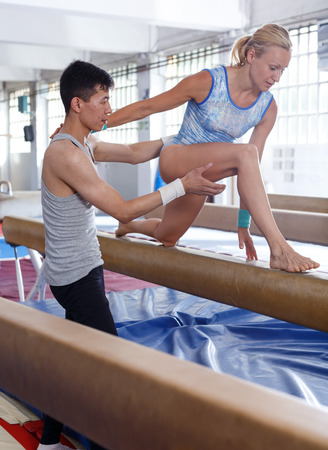 Woman gymnast in bodysuit training at broad bars in sport gym, man helping