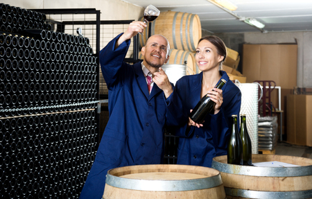 Two positive winery workers holding glass of wine in aging section of factory. Focus on the man