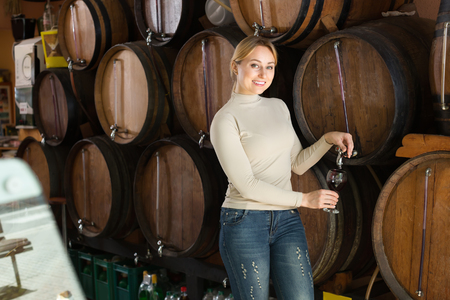 Smiling young woman pouring red wine from wood in wine house