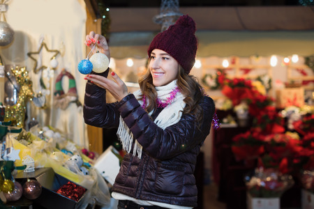 Positive young girl choosing xmas decoration at fair