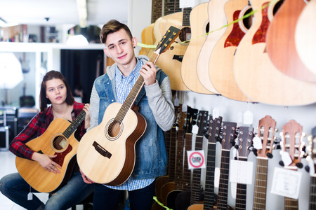 Smiling female and male teenagers examining acoustic guitars in guitar shop Stock Photo