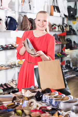 Young girl is choosing ballet shoes in shoes shop