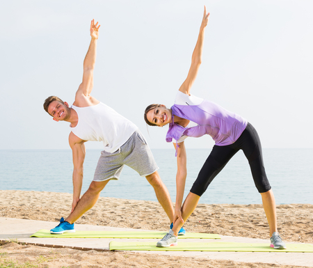 Smiling couple exercising yoga poses standing on sunny beach by ocean in morning 版權商用圖片