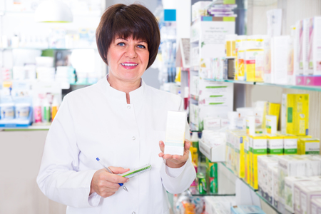 portrait of woman pharmacist wearing uniform and working in pharmaceutical shop Stock Photo