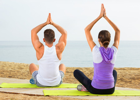Happy woman and man sitting cross-legged do yoga poses on beach at daytime