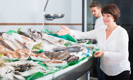 Man and woman purchasing chilled on ice fish in supermarket