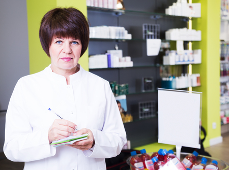Cheerful woman druggist wearing white uniform standing among shelves in pharmacy